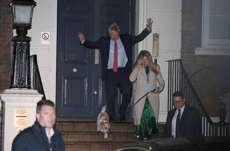 Britain's Prime Minister and Conservative Party leader Boris Johnson leaves Conservative Party headquarters with his partner Carrie Symonds and their dog Dilyn, in London, Friday, Dec. 13, 2019. Prime Minister Boris Johnson's Conservative Party appeared on course Friday to win a solid majority of seats in Britain's Parliament— a decisive outcome to a Brexit-dominated election that should allow Johnson to fulfill his plan to take the U.K. out of the European Union next month.