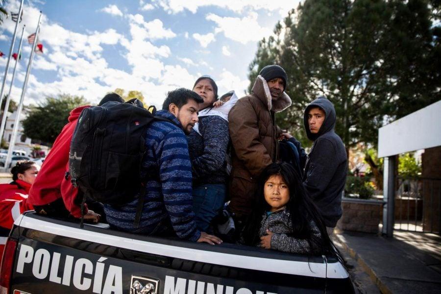 Solicitantes de asilo político se sientan detrás de un vehículo policial después de ser deportados a Nogales, Sonora México.
