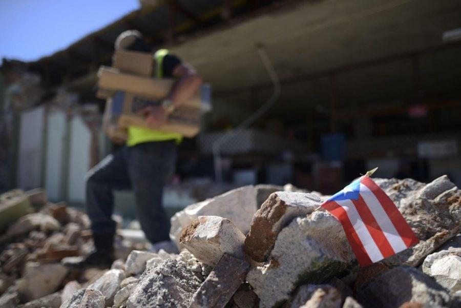 Una+bandera+puertorrique%C3%B1a+cuelga+entre+los+escombros%2C+donde+los+due%C3%B1os+de+las+tiendas+y+familiares+ayudan+a+retirar+provisiones+de+la+ferreter%C3%ADa+Ely+Mer+Mar%2C+que+se+derrumb%C3%B3+parcialmente+despu%C3%A9s+de+un+terremoto+en+Gu%C3%A1nica%2C+Puerto+Rico.+