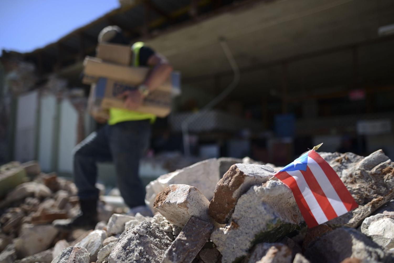 Una bandera puertorriqueña cuelga entre los escombros, donde los dueños de las tiendas y familiares ayudan a retirar provisiones de la ferretería Ely Mer Mar, que se derrumbó parcialmente después de un terremoto en Guánica, Puerto Rico.
