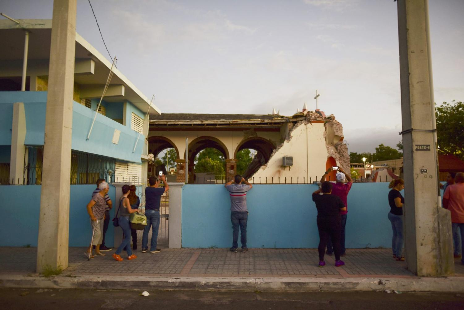 People take pictures of the Immaculate Concepcion Catholic church hours after a magnitude 5.9 earthquake, following a previous earthquake earlier in the week collapsed part of the church in Guanica, Puerto Rico.