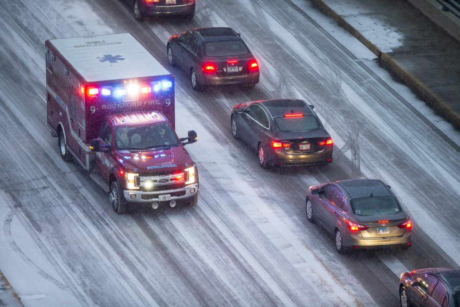 Snow falls as traffic moves slowly along State Street ahead of the Jeff Dunham comedy show at the BMO Harris Bank Center Saturday, Jan. 11, 2020, in downtown Rockford, Ill.
