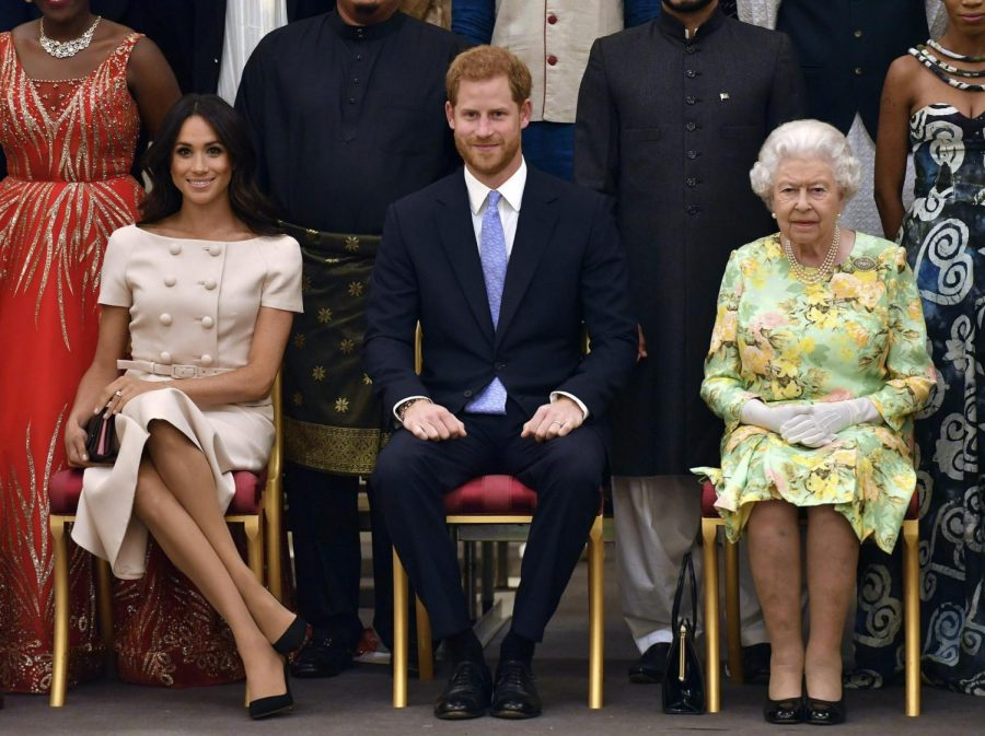 In this Tuesday, June 26, 2018 file photo Britain's Queen Elizabeth, Prince Harry and Meghan, Duchess of Sussex pose for a group photo at the Queen's Young Leaders Awards Ceremony at Buckingham Palace in London. Prince Harry and Meghan Markle are to no longer use their HRH titles and will repay £2.4 million of taxpayer's money spent on renovating their Berkshire home, Buckingham Palace announced Saturday, Jan. 18. 2020.