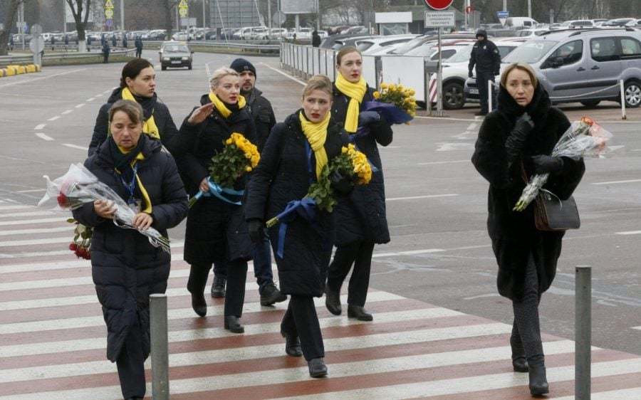 A crew of a Ukrainian airlines carry flowers to pay tribute to the flight crew members of the Ukrainian 737-800 plane that crashed on the outskirts of Tehran, arrive for memorial service at Borispil international airport outside Kyiv, Ukraine, Sunday, Jan. 19, 2020. An Ukrainian passenger jet carrying 176 people has crashed just minutes after taking off from the Iranian capital's main airport on Jan. 8, 2020.