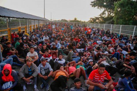 Migrantes hondureños esperan en el puente, el cruce fronterizo legal, que cruza el río Suchiate en Tecun Uman, en la frontera de Guatemala con México, al amanecer del lunes 20 de enero de 2020.