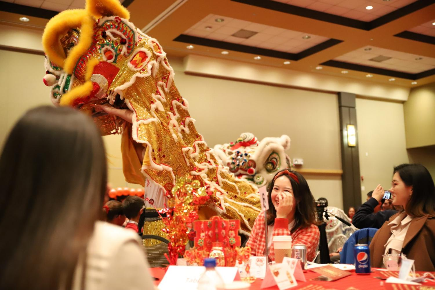 Three women sit at a table and laugh at the celebratory dragon passing by. The Chinese New Year event featured networking, games and a buffet, in addition to performances.