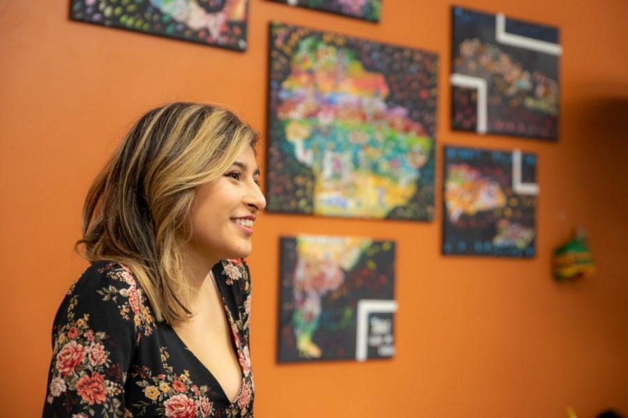 Lupe Casas habla frente al mural que creó para el centro cultural latinx.
