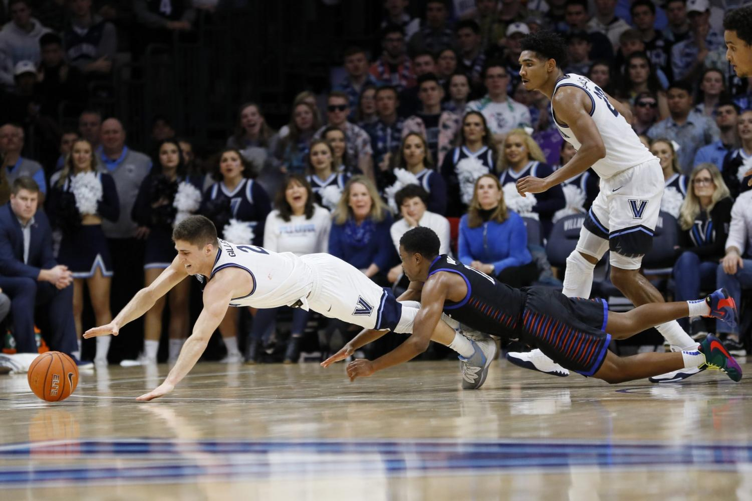 Villanova's Collin Gillespie dives for a loose ball with DePaul's Charlie Moore during the second half in their game on Tuesday night in Villanova, Pa. Villanova won 79-75 in overtime.