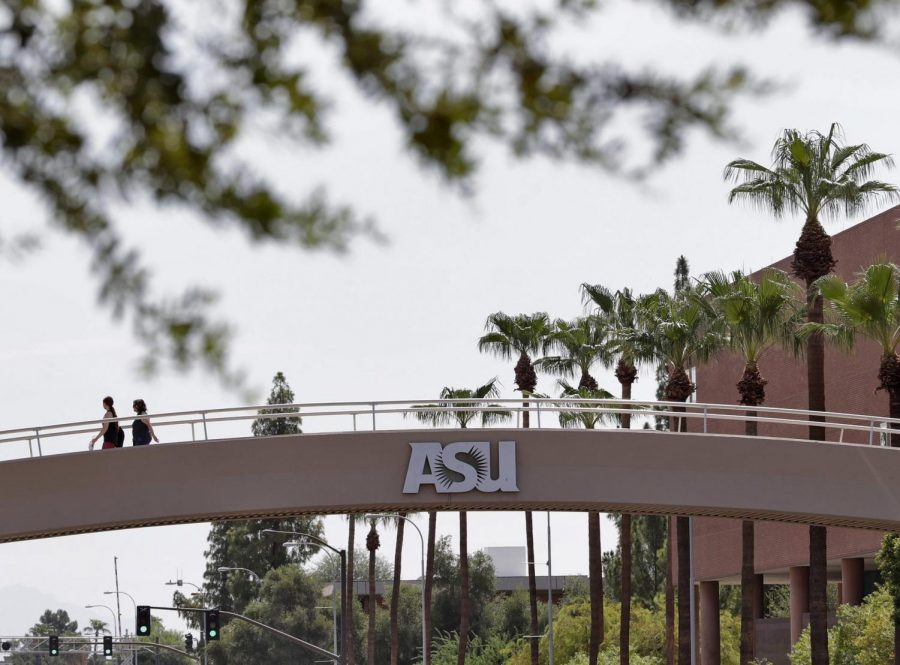 In this July 25, 2018, file photo, pedestrians cross over University Avenue on the campus of Arizona State University in Tempe, Ariz. As concerns about China's virus outbreak spread, universities all over the world are scrambling to assess the risks to their programs. One diagnosis was confirmed at ASU and another at the University of Massachusetts at Boston, which said the infected student had recently traveled to Wuhan.