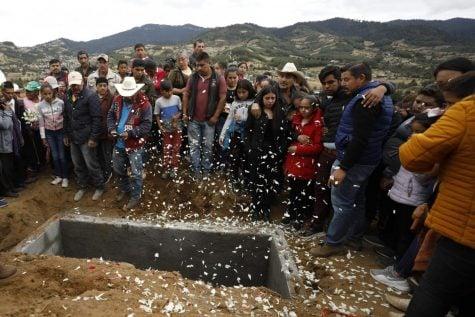 Los pétalos de las flores caen cuando familiares y amigos lloran alrededor de la tumba del activista comunitario Homero Gómez González en Ocampo, estado de Michoacán, México.