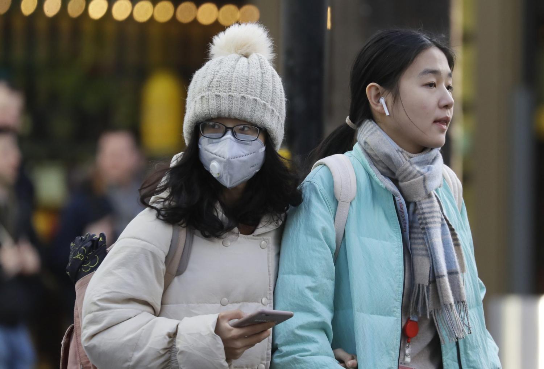 A woman wears a mask as she walks near Chinatown in London.