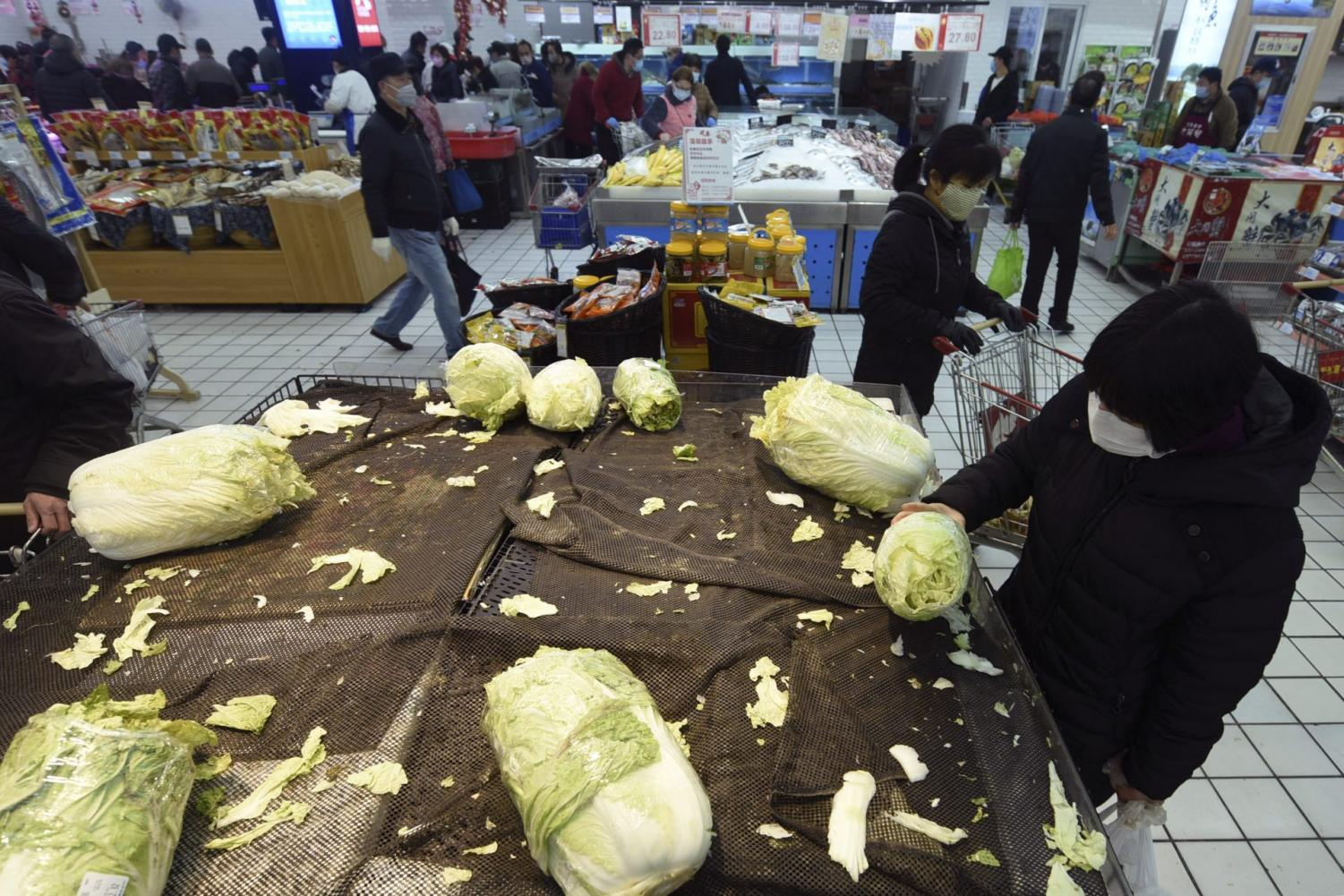 A woman, right, wears a face mask selects cabbage at a supermarket in Hangzhou in east China's Zhejiang province, Saturday, Feb. 8, 2020. China's communist leaders are striving to keep food flowing to crowded cities despite anti-disease controls, to quell fears of possible shortages and stave off price spikes from panic buying after most access to Wuhan was cut off Jan. 23. Food stocks in supermarkets ran low shortly after Beijing imposed travel curbs and extended the Lunar New Year holiday to keep factories, offices and other businesses closed and the public at home, attempting to prevent the virus from spreading.