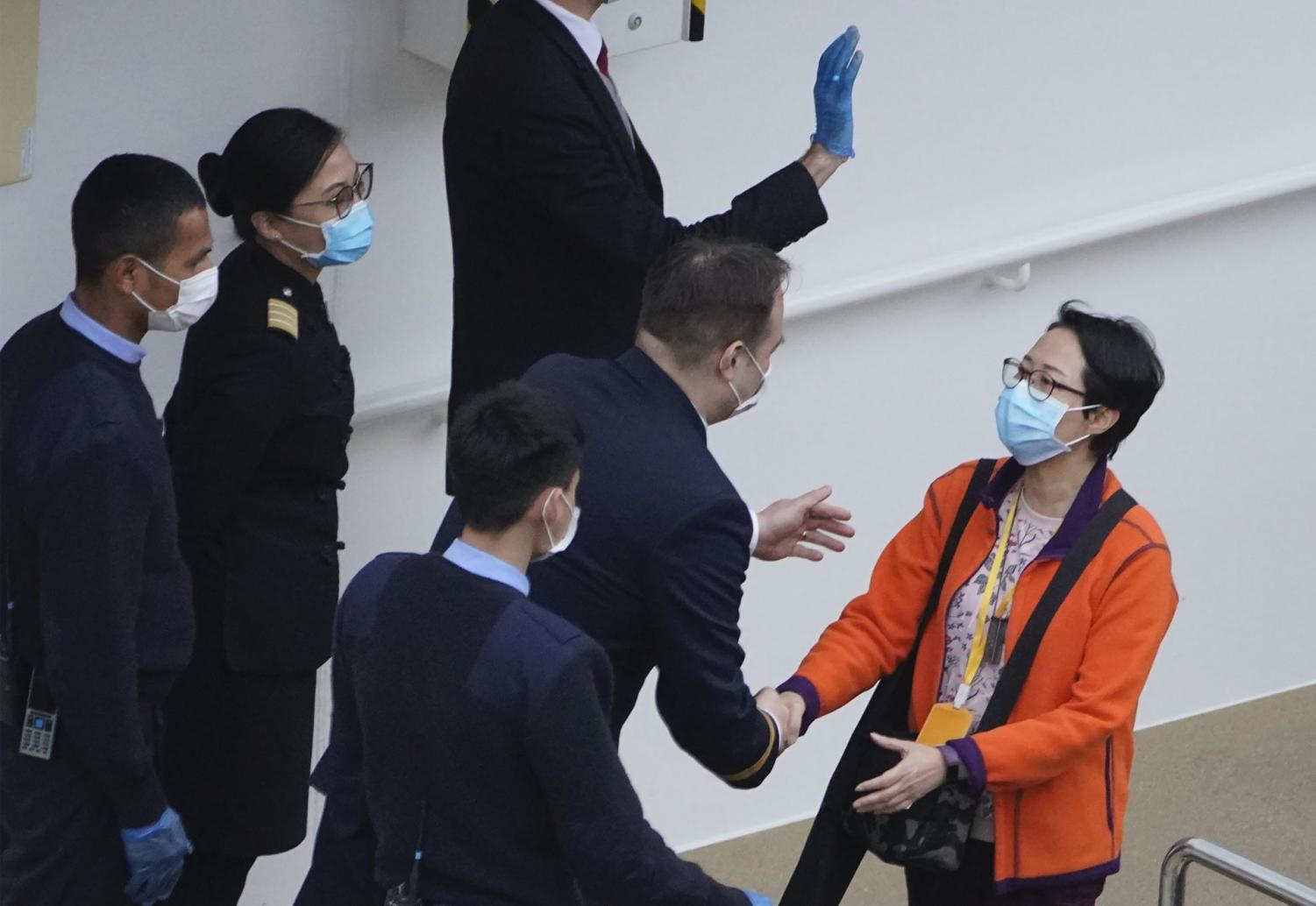 A passenger from the cruise ship World Dream docked at Kai Tak cruise terminal shakes hands with staff as she disembarks the ship after be quarantined for the coronavirus in Hong Kong, Sunday, Feb. 9, 2020. Several passengers from mainland China on a previous World Dream cruise were found to have the new coronavirus on returning home.