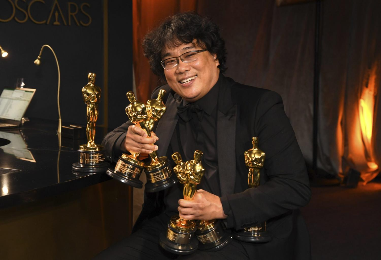 Bong Joon-ho holds the Oscars for best original screenplay, best international feature film, best directing, and best picture for