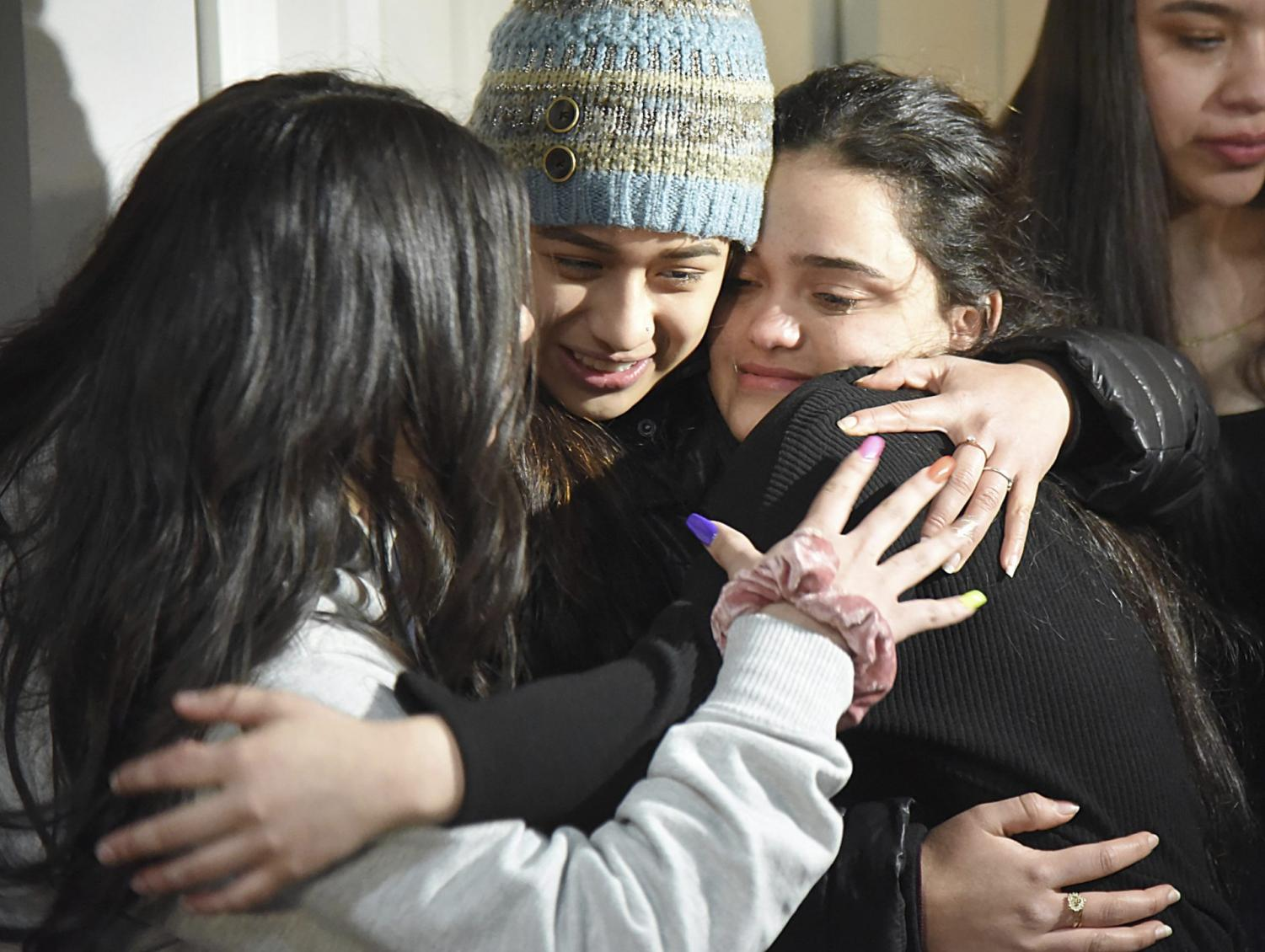 Meydi Guzman, right, a Crystal Lake Central High School senior who was in U.S. Immigration and Customs custody for several months, embraces friends as she is welcomed back at the home of school counselor Sara Huser on Thursday, Feb. 13, 2020, in Crystal Lake, Ill. Guzaman's supporters plan to continue a fight against her deportation to Honduras.