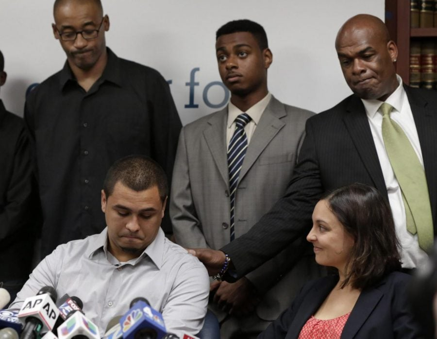 In this Aug. 12, 2013 file photo, plaintiff in the stop and frisk case David Ourlicht, seated left, is comforted by Merault Almonar, standing at right, father of plaintiff Devin Almonar, standing center, during a news conference at the Center for Constitutional Rights, in New York, after . U.S. District Judge Shira Scheindlin ruled that the New York Police Department deliberately violated the civil rights of tens of thousands of New Yorkers with its contentious stop-and-frisk policy. Standing at left is plaintiff Leroy Downes while attorney Jenn Borchetta listens, seated right.