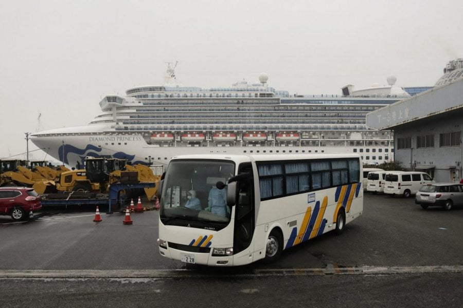A bus leaves the quarantined Diamond Princess cruise ship at a port Sunday, Feb. 16, 2020, in Yokohama, near Tokyo. The U.S. says Americans aboard a quarantined ship will be flown back home on a chartered flight Sunday, but that they will face another two-week quarantine.