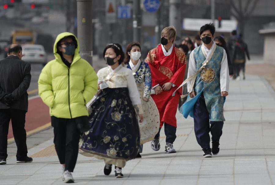 Visitors wearing face masks walk near the Gwanghwamun, the main gate of the 14th-century Gyeongbok Palace, and one of South Korea's well-known landmarks, in Seoul, South Korea, Saturday, Feb. 22, 2020. South Korea's Vice Health Minister Kim Gang-lip says the outbreak has entered a serious new phase but expressed cautious optimism that it can be contained to the region surrounding Daegu, where the first case was reported on Tuesday.