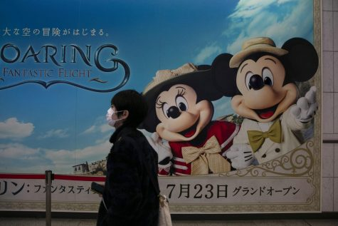 A man wearing a mask walks past an advertisement for the Tokyo Disney Resort at a train station in Urayasu, near Tokyo, Friday, Feb. 28, 2020. The amusement park will be closed from Feb. 29 until March 15 in an effort to prevent the spread of COVID-19.