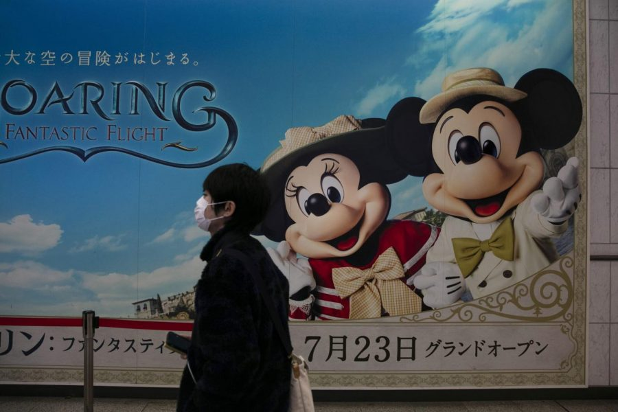 A+man+wearing+a+mask+walks+past+an+advertisement+for+the+Tokyo+Disney+Resort+at+a+train+station+in+Urayasu%2C+near+Tokyo%2C+Friday%2C+Feb.+28%2C+2020.+The+amusement+park+will+be+closed+from+Feb.+29+until+March+15+in+an+effort+to+prevent+the+spread+of+COVID-19.