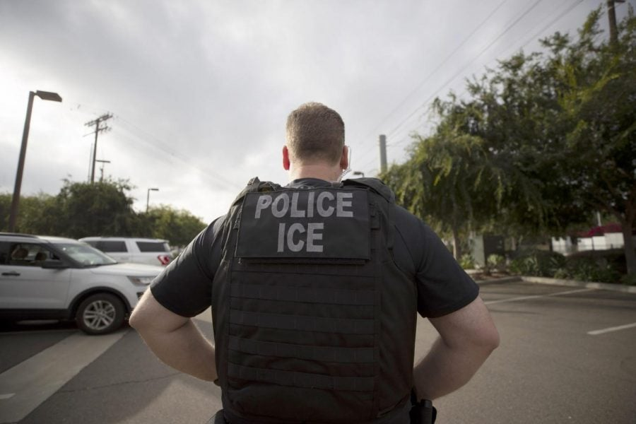 In this July 8, 2019, file photo, a U.S. Immigration and Customs Enforcement (ICE) officer looks on during an operation in Escondido, Calif.
