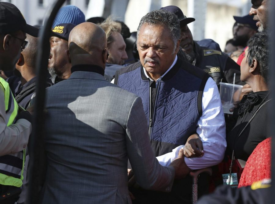 The Rev. Jesse Jackson is helped across the Edmund Pettus Bridge, Sunday, March 1, 2020, in Selma, Ala.