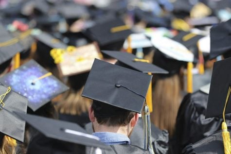 FILE- In this May 5, 2018, file photo, students attend the University of Toledo commencement ceremony in Toledo, Ohio. Colleges across the U.S. have begun cancelling and curtailing spring graduation events amid fears that the new coronavirus will not have subsided before the stretch of April and May when schools typically invite thousands of visitors to campus to honor graduating seniors.