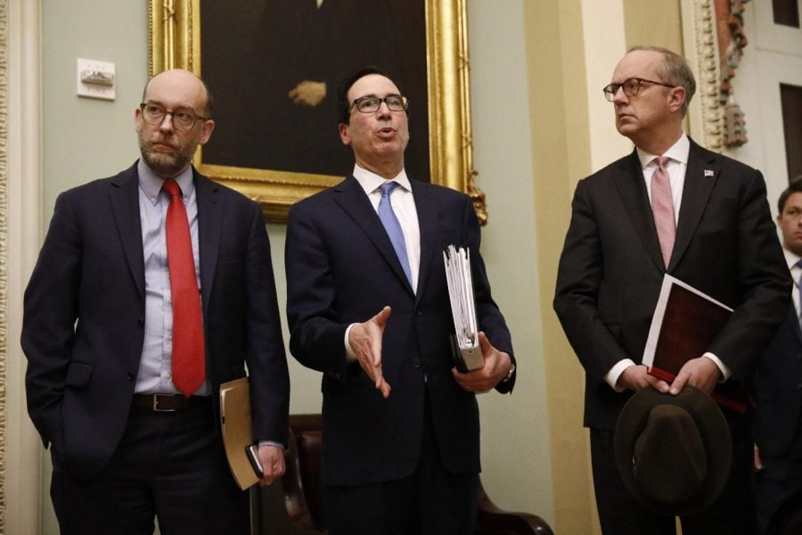 Treasury Secretary Steve Mnuchin, center, speaks with members of the media as he departs a meeting with Senate Republicans on an economic lifeline for Americans affected by the coronavirus outbreak. on Capitol Hill in Washington, Monday, March 16, 2020.