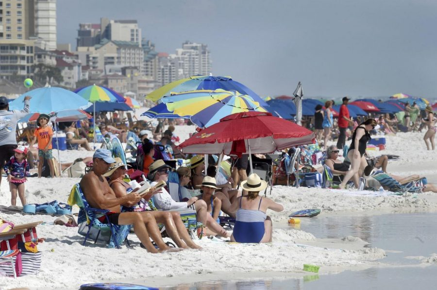 People gather on the shoreline in Destin, Fla., Wednesday, March 18, 2020.