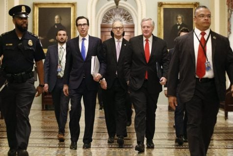 Treasury Secretary Steven Mnuchin, left, accompanied by White House Legislative Affairs Director Eric Ueland and acting White House chief of staff Mark Meadows, walks to the offices of Senate Majority Leader Mitch McConnell of Ky. on Capitol Hill in Washington, Tuesday, March 24, 2020.