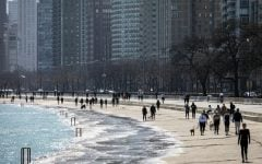 Residents enjoy the warm weather with a stroll along the Lakefront Trail near Oak Street Beach, Wednesday afternoon, March 25, 2020, in Chicago, despite a stay-at-home order from Illinois Gov. J.B. Pritzker during the coronavirus pandemic. The new coronavirus causes mild or moderate symptoms for most people, but for some, especially older adults and people with existing health problems, it can cause more severe illness or death.