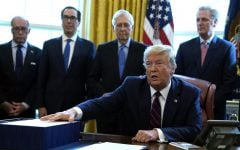 President Donald Trump speaks before he signs the coronavirus stimulus relief package in the Oval Office at the White House, Friday, March 27, 2020, in Washington. Listening are from left, Larry Kudlow, White House chief economic adviser, Treasury Secretary Steven Mnuchin, Senate Majority Leader Mitch McConnell, R-Ky., and House Minority Leader Kevin McCarty of Calif.