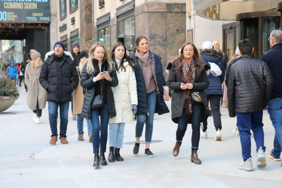 A group of women walk down Michigan Ave. near Nordstroms.