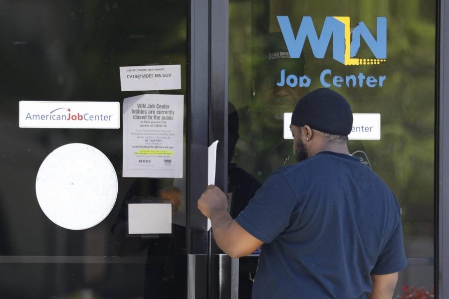 Tyrone Keoton Jr., is handed an unemployment benefit application form by a security guard behind the glass doors of this state WIN Job Center in north Jackson, Miss., Thursday, April 2, 2020. The job centers lobbies are closed statewide to prevent the spread of COVID-19. The agency encourages residents to apply for their benefits on line, however, the system has been stressed by the large numbers of applicants. The local job centers are making paper unemployment applications available and applicants are filling them out and pushing them back through the mail slots or doors as well as they can.