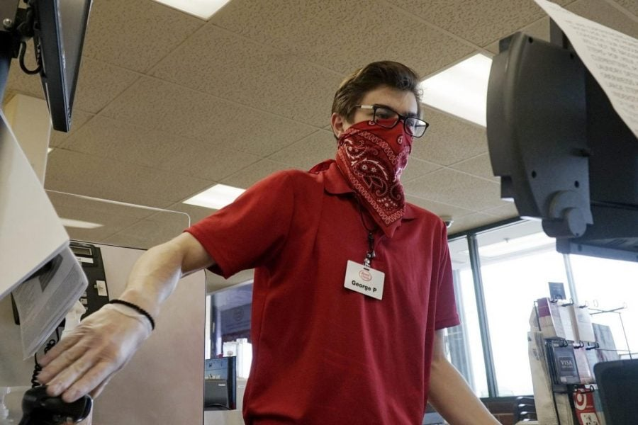 Un cajero trabaja en una caja registradora mientras se cubre la cara con un pañuelo en el supermercado de Jewel Osco en Mount Prospect, Illinois.