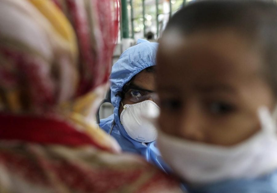 A doctor engages with people at a slum area during lockdown to control the spread of the new coronavirus in Mumbai, India, Tuesday, April 7, 2020. . The new coronavirus causes mild or moderate symptoms for most people, but for some, especially older adults and people with existing health problems, it can cause more severe illness or death.