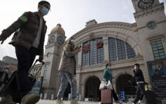 Travelers with their luggage walk past the Hankou railway station on the eve of its resuming outbound traffic in Wuhan in central China's Hubei province on Tuesday, April 7, 2020. Starting Wednesday, residents of Wuhan will be allowed to once again travel in and out of the sprawling city where the coronavirus pandemic began, ending an 11-week lockdown.