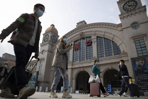 Travelers with their luggage walk past the Hankou railway station on the eve of its resuming outbound traffic in Wuhan in central China