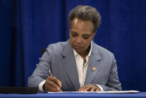 Chicago Mayor Lori Lightfoot signs an executive order to ensure coronavirus-related benefits offered by the city of Chicago are available to immigrants and refugees, Tuesday morning, April 7, 2020.