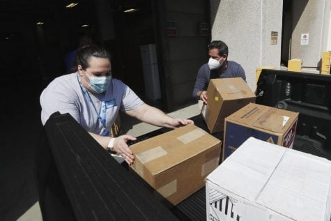 Christina Caldwell, left, of Henry Ford Population Health helps unload supplies with Matt Thatcher, who donated them from the Detroit Golf Club, Wednesday, April 8, 2020, in Detroit. The hospital is also in need of gowns and other PPE items and hopes more donations will be coming in from others to help during the coronavirus pandemic.