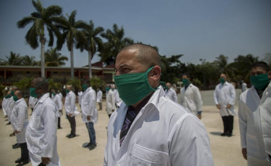 Cuban doctors form up during a farewell ceremony as they get ready to leave for Italy to help with the new coronavirus pandemic, in Havana, Cuba.