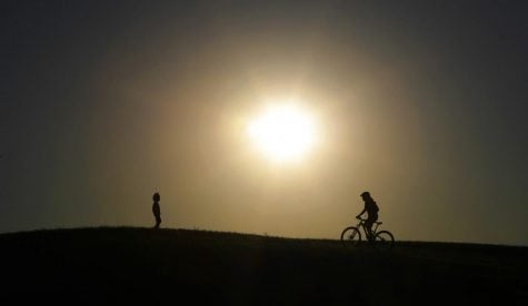 A cyclist tops a hill in a park at sunset in San Antonio, Monday, April 13, 2020. San Antonio is under stay-at-home orders due to the coronavirus pandemic, but parks have remained open for exercise and physical activity as long as social distancing is observed.