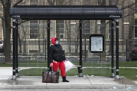 A woman waits at a Chicago Transit Authority bus shelter during the coronavirus pandemic on the city's West Side Wednesday, April 15, 2020.