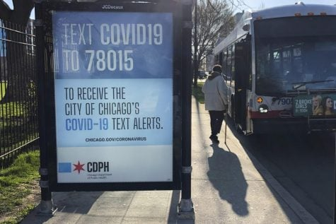 A lone woman boards a Chicago Transit Authority bus in the Bronzeville neighborhood of Chicago, Monday, April 20, 2020, as a public service billboard reminds people of the continuing fight against COVID-19.