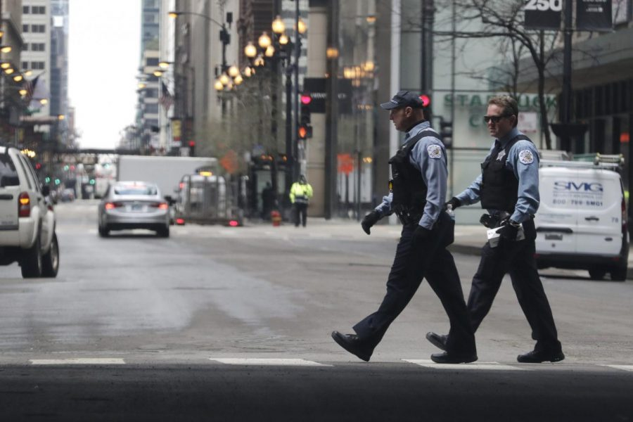Chicago Police officers cross the street in downtown Chicago, Wednesday, April 22, 2020.