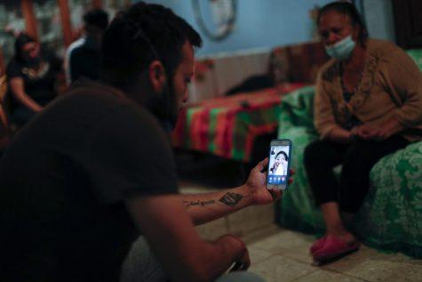 El nieto Gustavo Briseno Pinera comparte una videollamada con una nieta que llora, que vive cerca pero solo pudo estar presente por teléfono debido a la pandemia de coronavirus, ya que los miembros de la familia lloran a Manuel Briseno Espino, de 78 años, quien murió por complicaciones debido a COVID-19.