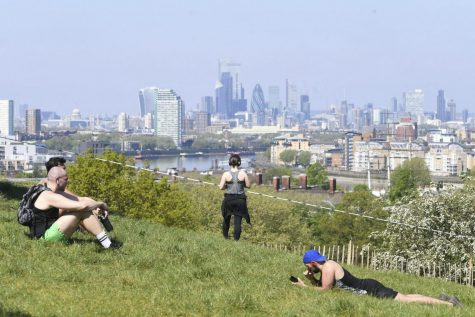 People sit on the grass in Greenwich Park, London as the UK continues in lockdown to help curb the spread of the coronavirus, Sunday April 26, 2020. The highly contagious COVID-19 coronavirus has impacted on nations around the globe, many imposing self isolation and exercising social distancing when people move from their homes.
