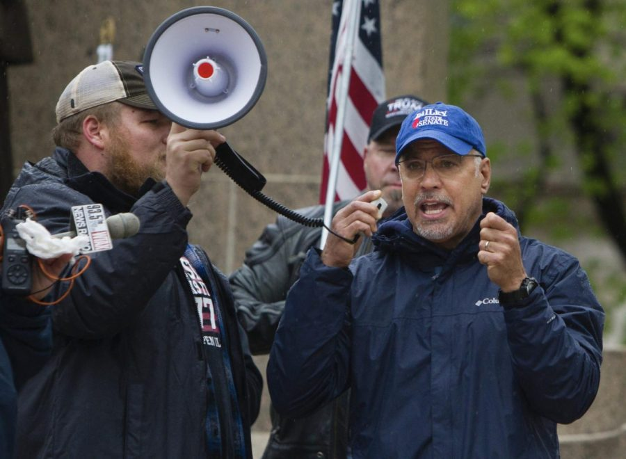 In this April 25, 2020 file photo, Illinois State Rep. Darren Bailey, R-Xenia, right, speaks at a protest against Gov. J.B. Pritzker's stay-at-home order in front of the Capitol building in Springfield, Ill., during the coronavirus outbreak. A judge in southern Illinois ruled Monday, April 27, 2020, that Pritzker's stay-at-home order to stem the spread of the coronavirus exceeds his emergency authority and violates individual civil rights.
