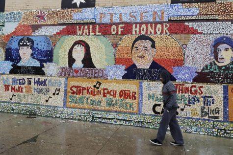 Un hombre camina en la acera junto a un mural, durante la pandemia COVID-19 en el barrio de Pilsen de Chicago.