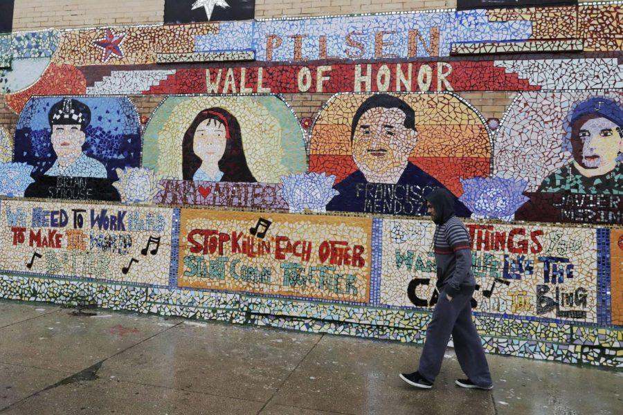 Un+hombre+camina+en+la+acera+junto+a+un+mural%2C+durante+la+pandemia+COVID-19+en+el+barrio+de+Pilsen+de+Chicago.+